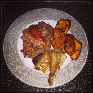 Boiled beans, tomato stew with palm oil, fried plantain and fried fish.